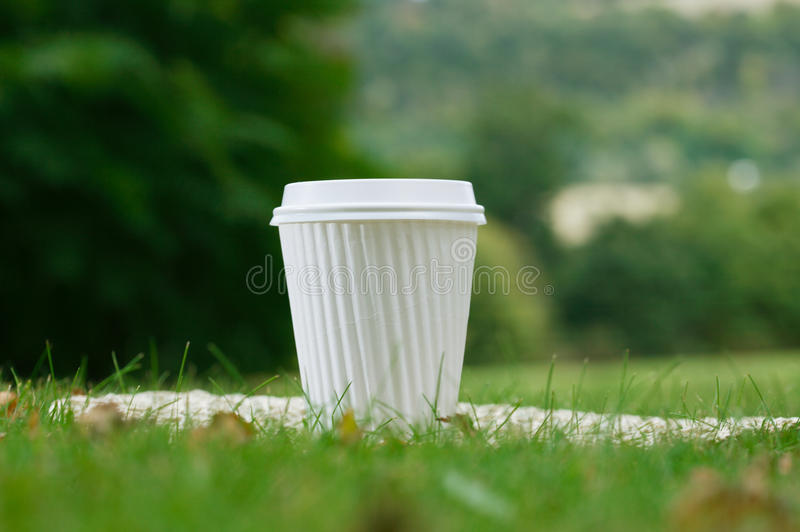 A white coffee cup in the grass. Shallow DOF stock photo