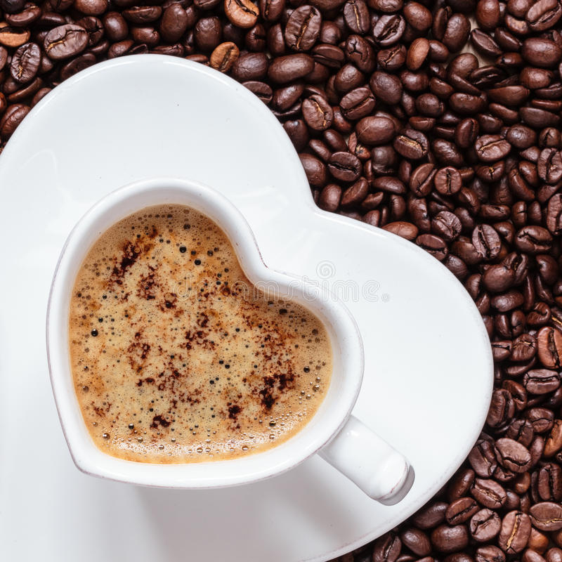 White coffee cup heart shaped with cappucino. Hot beverage. White coffee cup heart shaped with cappucino latte on roasted beans background royalty free stock photos