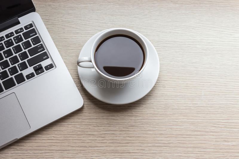 White coffee cup and laptop on wooden table top view. Close up white coffee cup and laptop on wooden table top view royalty free stock image