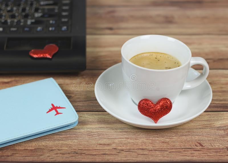 White coffee cup with red glitter heart on saucer on wooden table with computer notebook keyboard with red heart on it  and royalty free stock image
