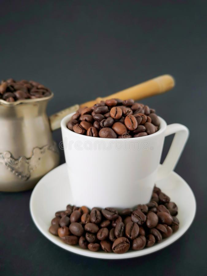 White coffee cup and saucer; coffee beans scattered on the table. In the background is a cezve. Black background. stock image