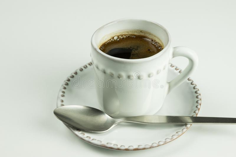 A white coffee cup full of black coffee and tea spoon on white saucer standing on white table as background. stock photos