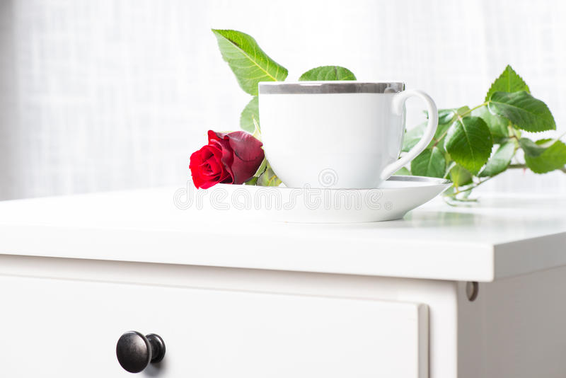 White coffee cup and single red rose
