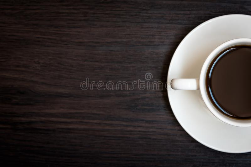 White coffee cup on wood table background with copy space, Half cup with full of coffee, Dark tone still life and vignette, Top royalty free stock image