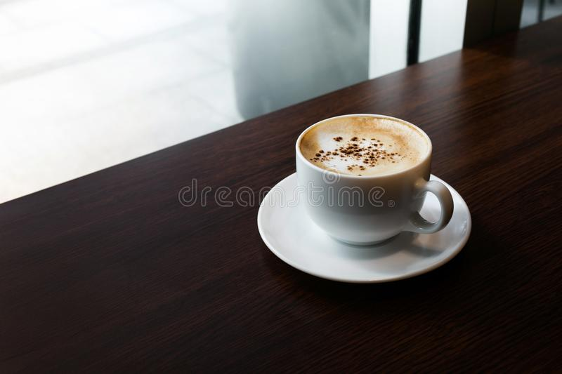White coffee cup on wooden desk table/nobody royalty free stock photo