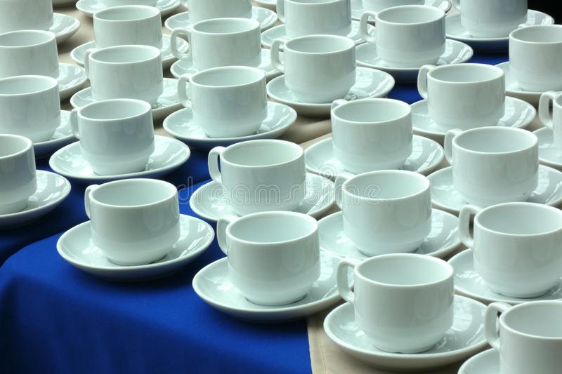 White Coffee Cups. Empty white coffee cups set on a table royalty free stock image