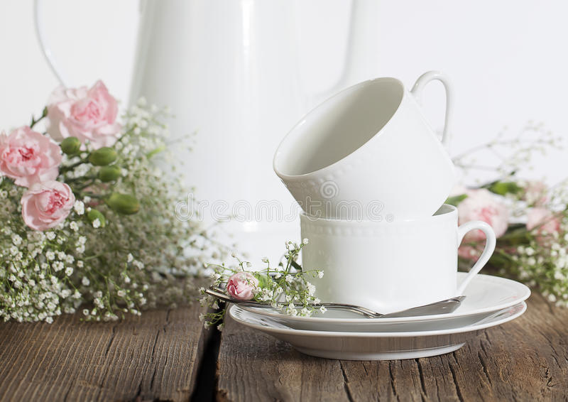 White Coffee Cups. Two white coffee cups stacked on white saucers on rustic board surface with white coffee pot, pink Carnations and white Gypsophila flowers stock photo
