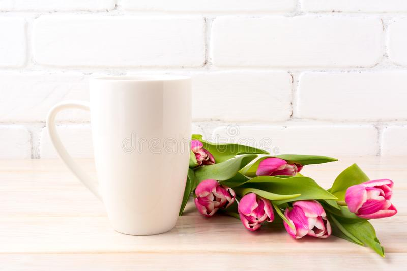 White coffee latte mug mockup with rich pink tulips bouquet royalty free stock photos