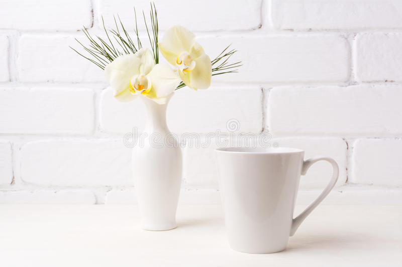 White coffee latte mug mockup with soft yellow orchid in vase. Empty mug mock up for design promotion stock photos