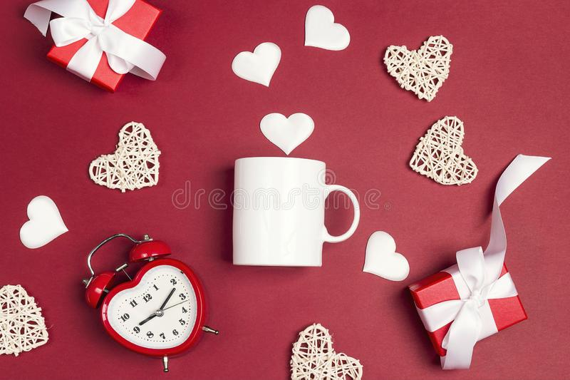 White coffee mug with alarm clock, gifts and decorative hearts on red background. Space for text or design stock photo