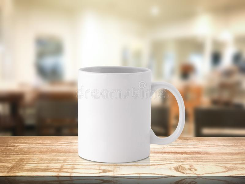 White coffee mug or drink cup on blur restaurant or desserts cafe interior store background. Wooden shelf backdrops with mugs for stock photo
