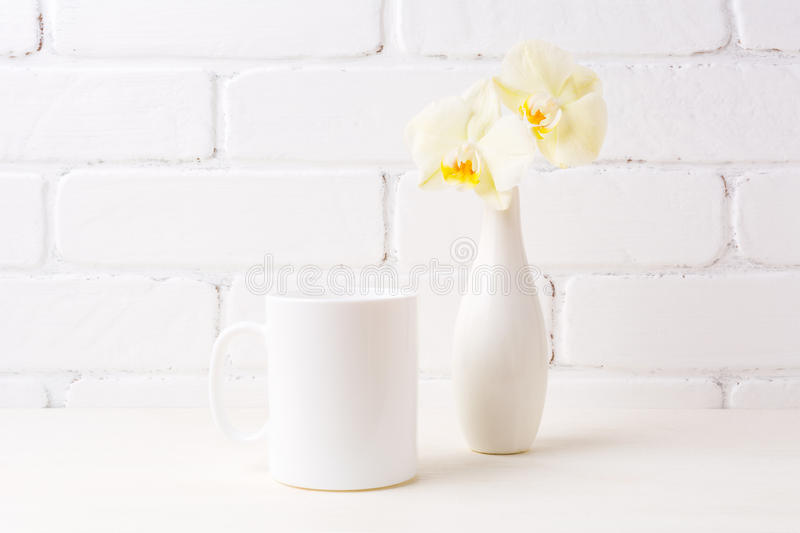 White coffee mug mockup with soft yellow orchid in vase royalty free stock images