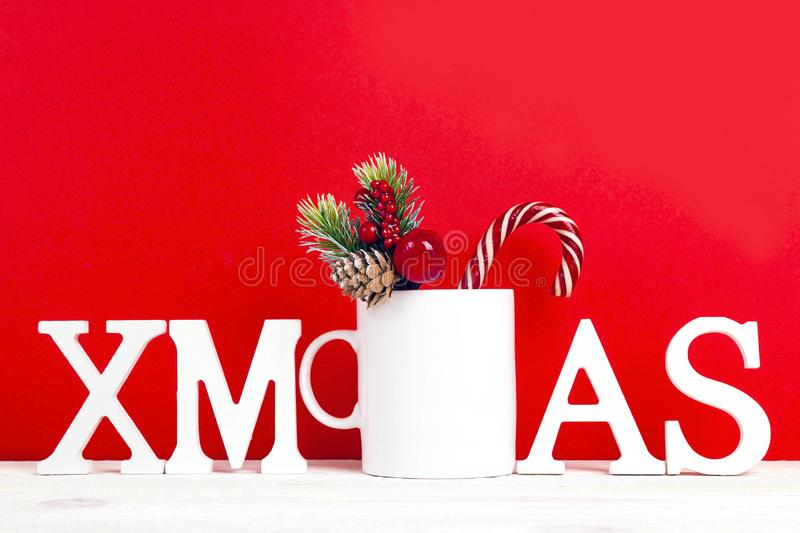 White coffee mug with word Xmas, candy cane and decorative branch on red background. stock image