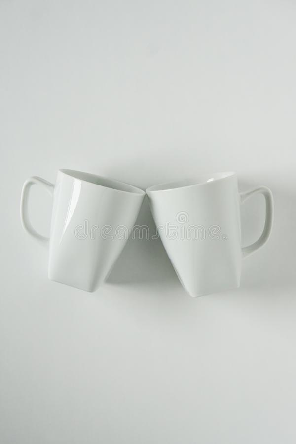 White coffee mugs on white background clinking in cheers with empty copy space stock image