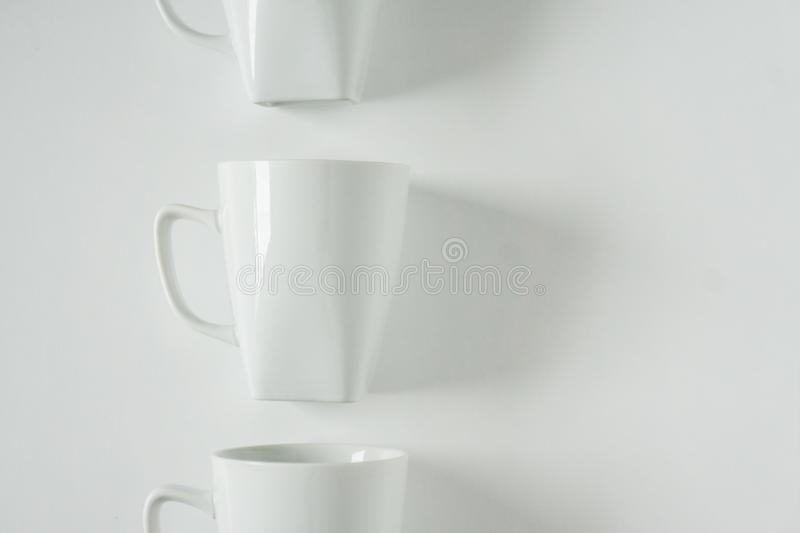 White coffee mugs on white background in a vertical row with empty copy space stock photos