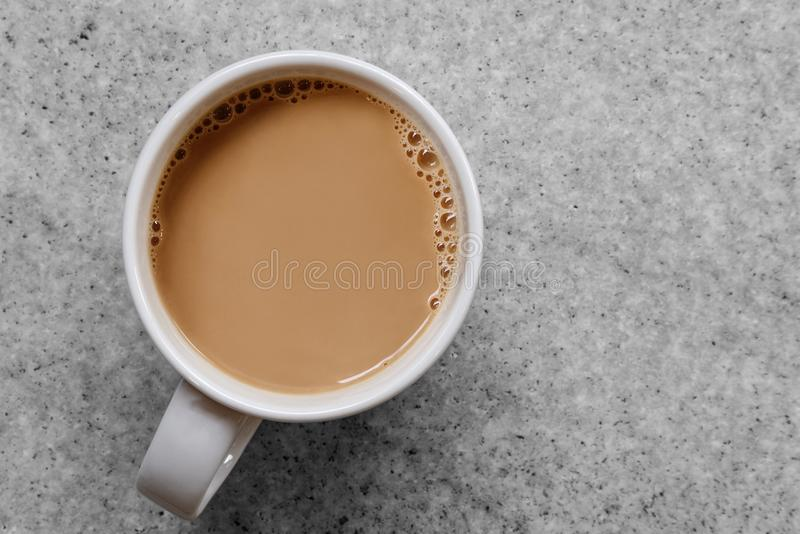 White coffee or tea with bubbles in white ceramic mug isolated o. N grey granite table from above stock images