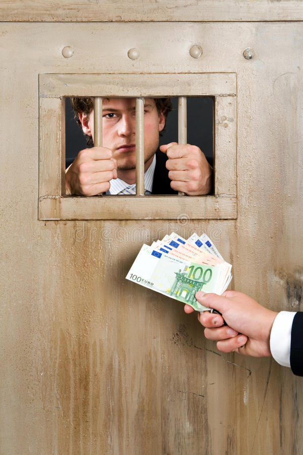 White Collar Criminal. Incarcerated white collar criminal, clutching the bars of a cell door, with a hand holding a substantial amount of cash as bribe royalty free stock photography