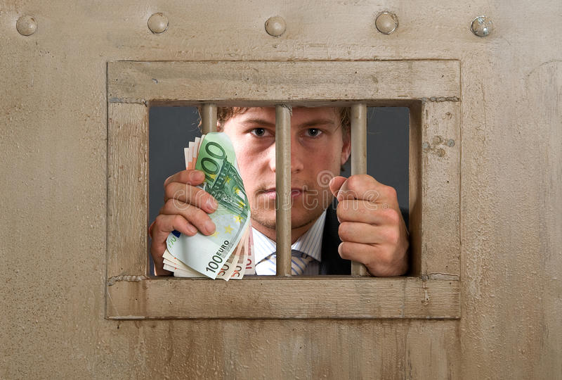 White collar criminal. In jail for fraud, holding the bars with a substantial amount of cash in his hands stock image
