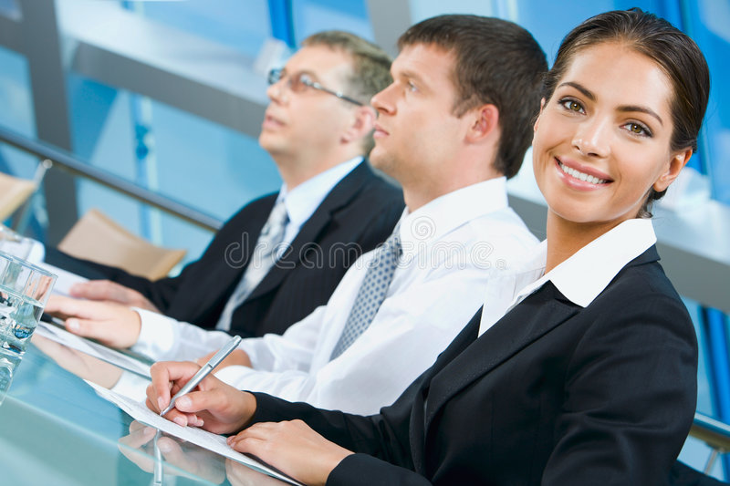 White collar worker. Pretty white collar worker is writing a text during business conference stock images