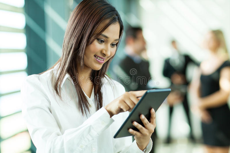 White collar worker. Beautiful indian white collar worker using tablet computer in office royalty free stock photography