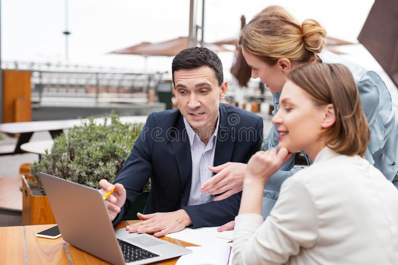White collar worker explaining actively work plan to his colleagues. White collar. Experienced white collar worker feeling curious while explaining actively royalty free stock image