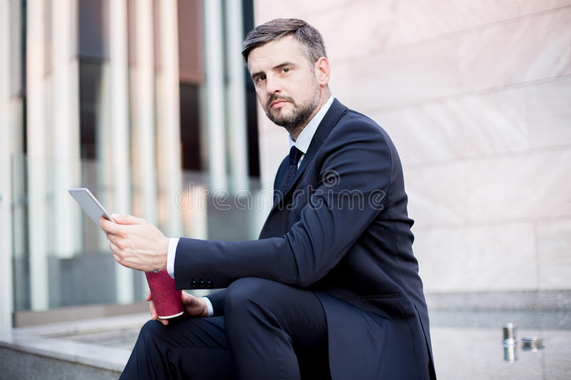 White collar worker laboring. Picture of white collar worker with tablet laboring outside stock image