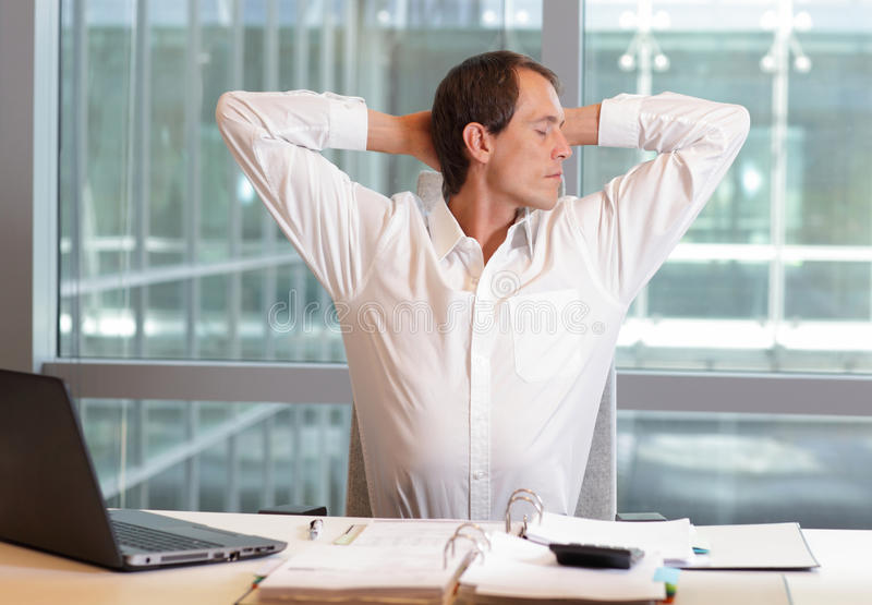 White collar worker male stretching arms. Relaxing neck - short break for exercise on chair in office stock photography