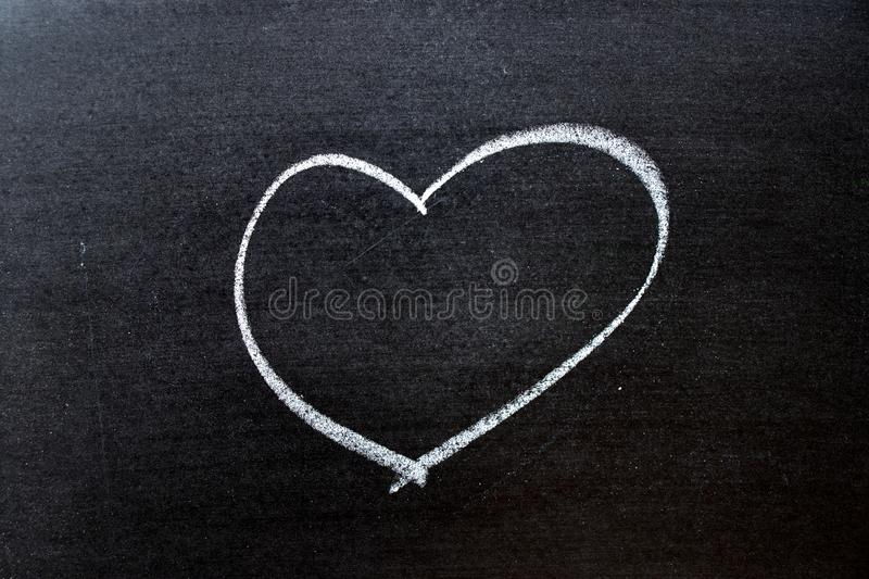 White coloe chalk drawing as heart shape on blackboard background with copy space stock photos