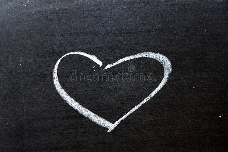 White coloe chalk drawing as heart shape on blackboard background. With copy space royalty free stock images