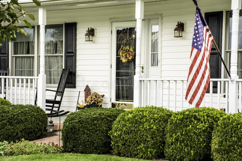 White Colonial Home With American Flag. White colonial home decorated for fall with American flag flying from the front porch with rocking chairs stock photo