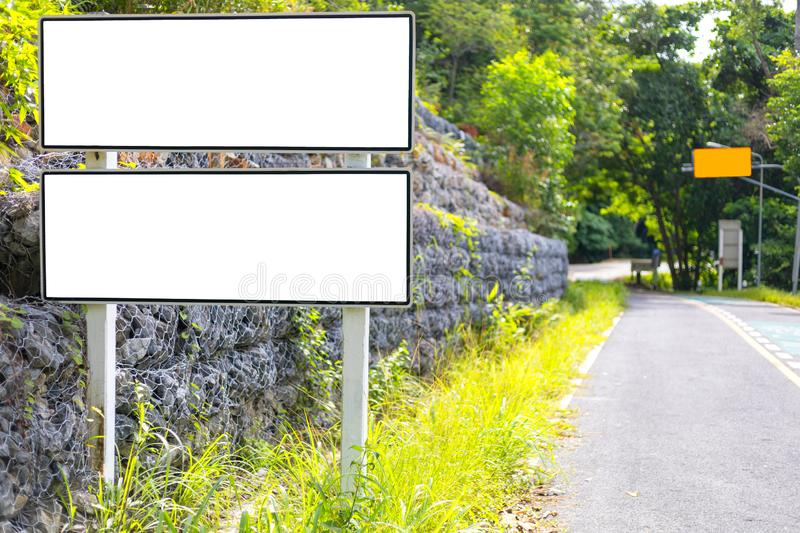 White color blank billboard or road sign on the road near green wood royalty free stock photos