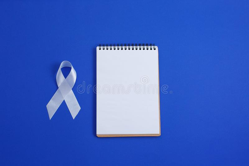 White color ribbon for raising awareness on Lung cancer and Multiple Sclerosis and international day of non-violence against stock image