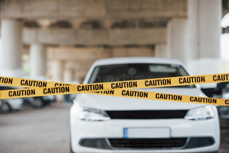 White colored automobile. Yellow caution tape near the car parking lot at daytime. Crime scene.  stock photography