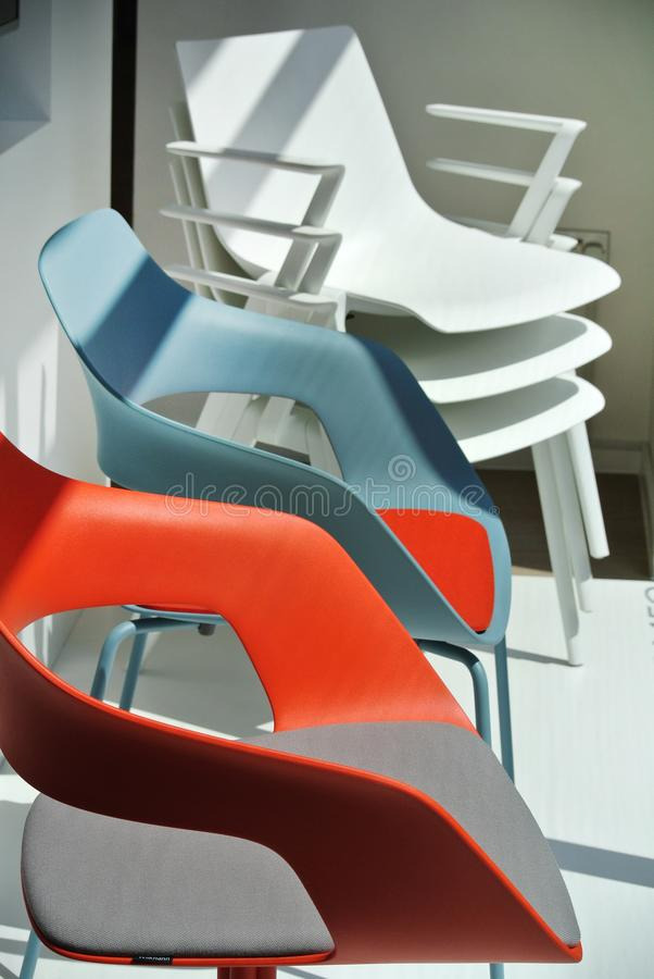 white and colored plastic chairs stock image