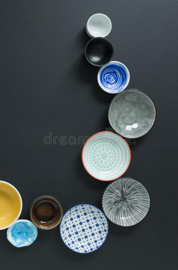 White and colorful tableware in different designs and sizes on black background, photographed from above in daylight royalty free stock photos