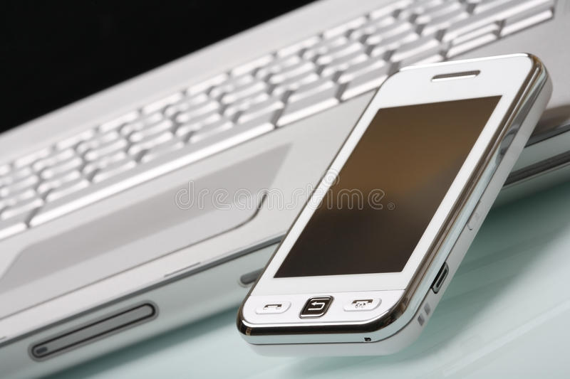 White communicator on silver laptop. White touch phone (communicator) on a high-end aluminium laptop. Shallow DOF, focus on a foreground. Modern communications stock images