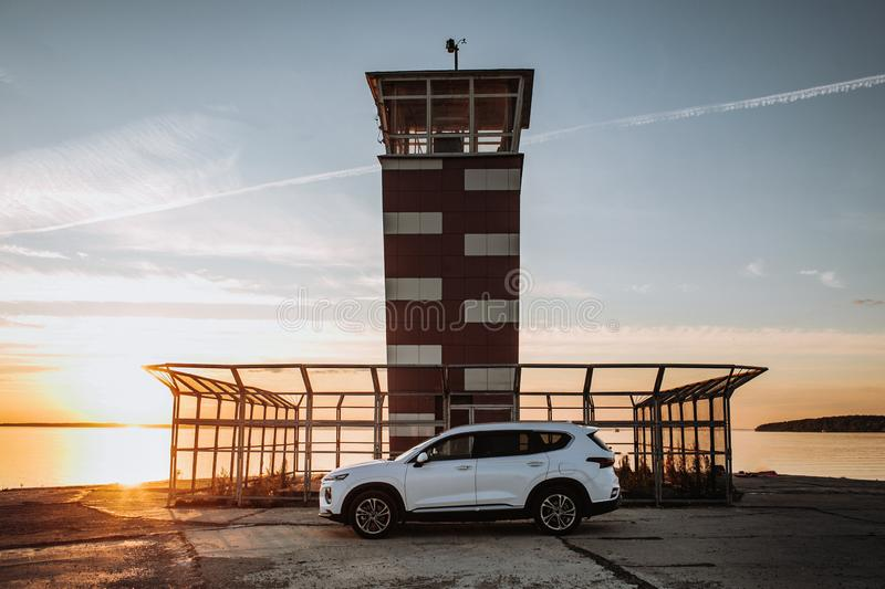 White compact SUV car with sport and modern design parked on concrete road by the sea near the beach at sunset royalty free stock image