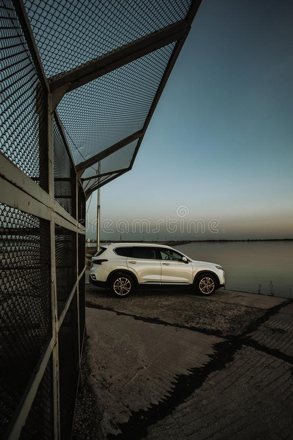 White compact SUV car with sport and modern design parked on concrete road by the sea near the beach at sunset stock images