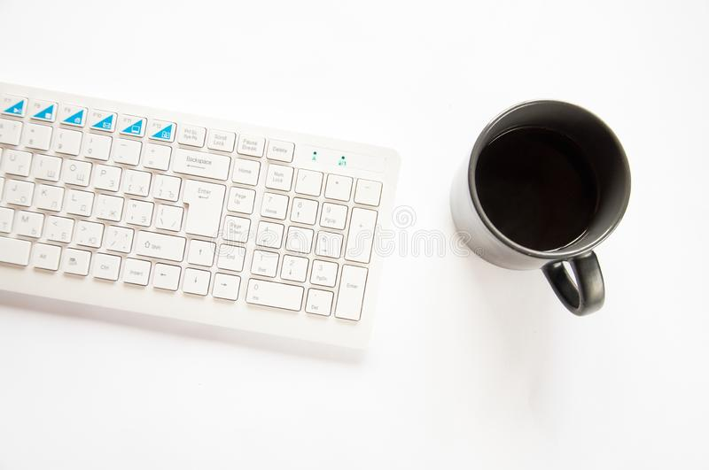 A white computer keyboard and a black cup of coffee are standing on the table against royalty free stock photo