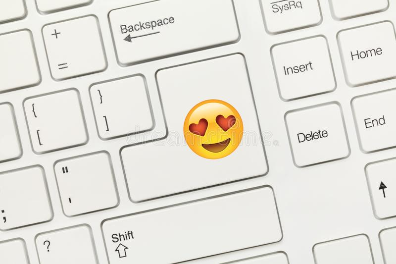 White conceptual keyboard - Key with Heart eyes Emoji symbol. Close-up view on white conceptual keyboard - Key with Heart eyes Emoji symbol stock images