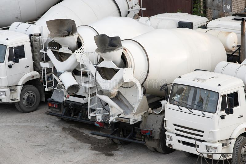 White concrete mixers are on the construction site. Truck, cement, industry, transportation, drive, heavy, lorry, vehicle, machine, pour, road, steel, work stock image