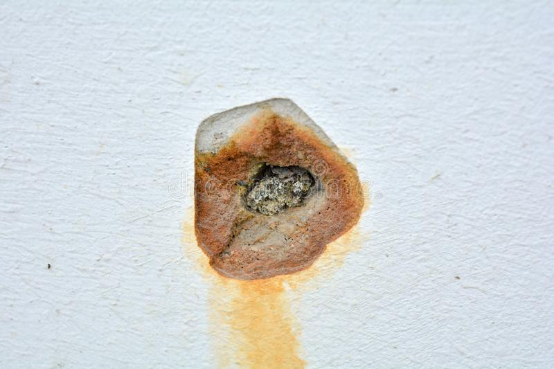 White concrete wall with rusted hole. Rust big dent on the roughness old house wall royalty free stock photos