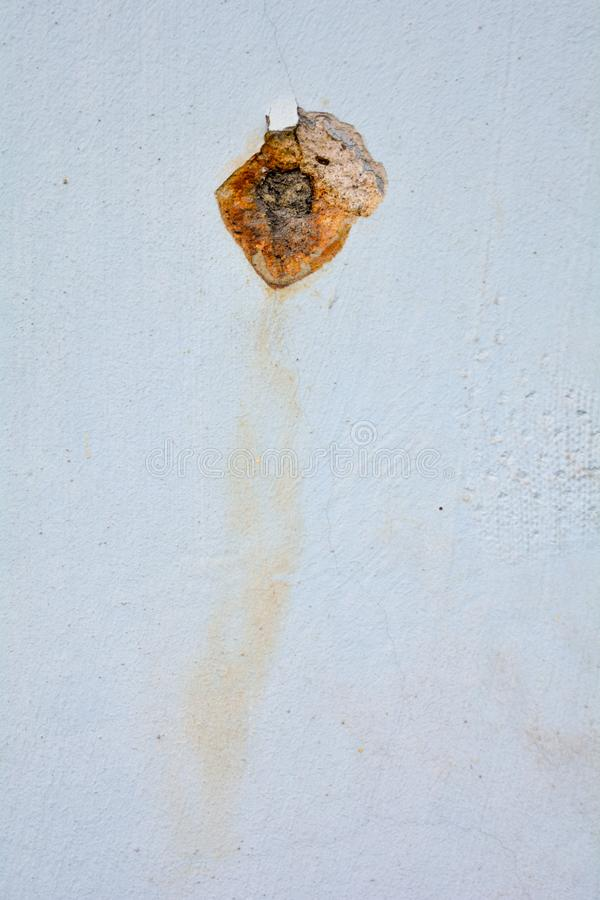 White concrete wall with rusted hole. Rust big dent on the roughness old house wall stock image