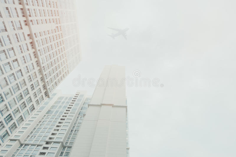 White contemporary residential skyscraper with a flying airplane. White contemporary residential skyscraper apartment building in Moscow on a cloudy day, with a stock photography