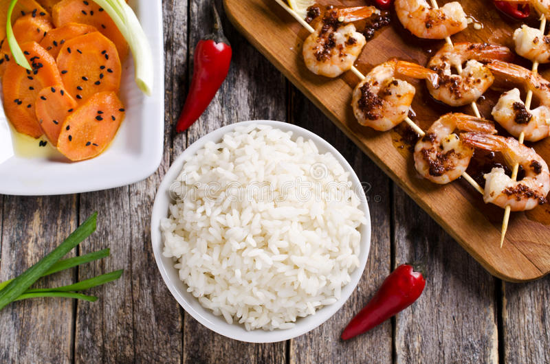 White cooked rice. White rice cooked on a background of shrimp on skewers and salad with carrots. Selective focus royalty free stock photo