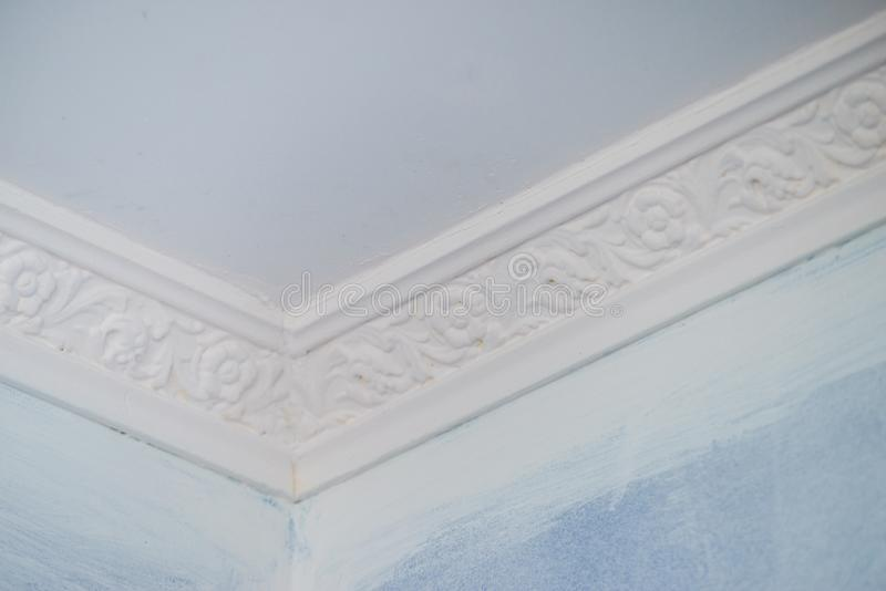 White cornce on wall. Decorative white cornice on blue wall, home room decor, design and architecture concept stock photography