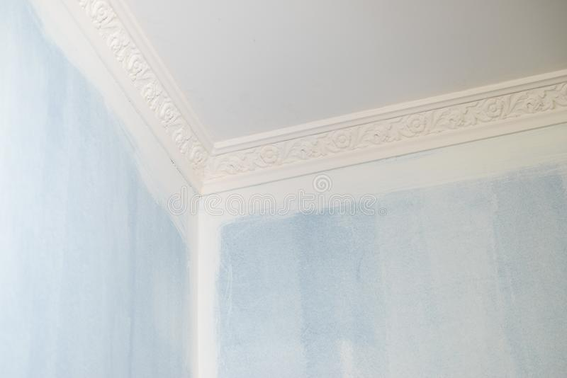 White cornce on wall. Decorative white cornice on blue wall, home room decor, design and architecture concept stock image
