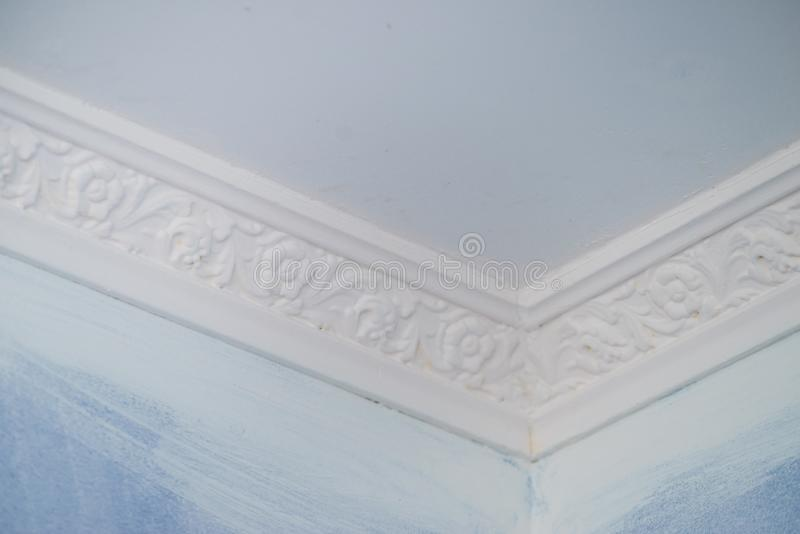 White cornce on wall. Decorative white cornice on blue wall, home room decor, design and architecture concept royalty free stock photography