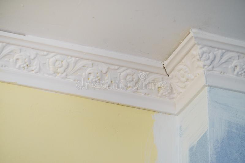 White cornce on wall. Decorative white cornice on blue and yellow wall, home room decor, design, architecture concept royalty free stock photo