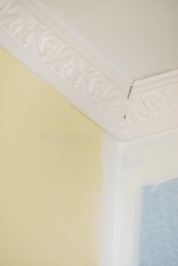 White cornce on wall. Decorative white cornice on blue and yellow wall, home room decor, design, architecture concept royalty free stock photos